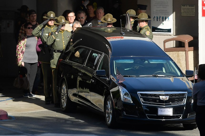 An honor guard salutes the body of Sgt. Ron Helus before it departs the Los Robles Regional Medical Center Thursday, Nov. 8, 2018, in Thousand Oaks, Calif. Helus was killed after a gunman opened fire the night before inside a country dance bar crowded with hundreds of people.