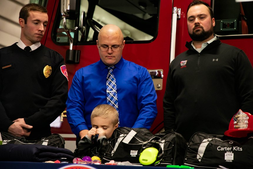 From left, Saginaw firefighter Brandon Hausbeck, Saginaw Township Police Detective Justin Severs and his son Carter, 5, and Andrew Keller stand together during a press conference unveiling the new Carter Kits at Saginaw Fire Department Station #1 on Thursday, Dec. 12, 2019. (Photo/Rachel Ellis, MLive.com)