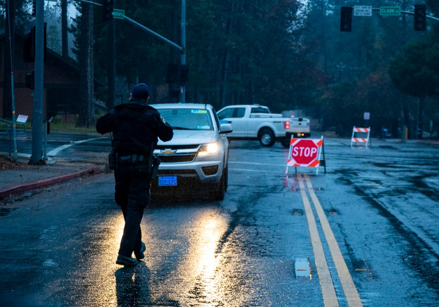 Paradise Police Officer Perry Walters assists a PG&E worker who's trying to get around many of the street closures on Nov. 27, 2018 in Paradise, Calif. (Gina Ferazzi/Los AngelesTimes/TNS)