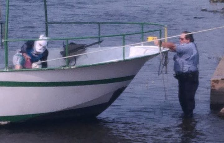 A police officer aims a TASER at a masked man accused of stealing a boat fromNicollet IslandinMinneapolis. (Photo/Star Tribune)