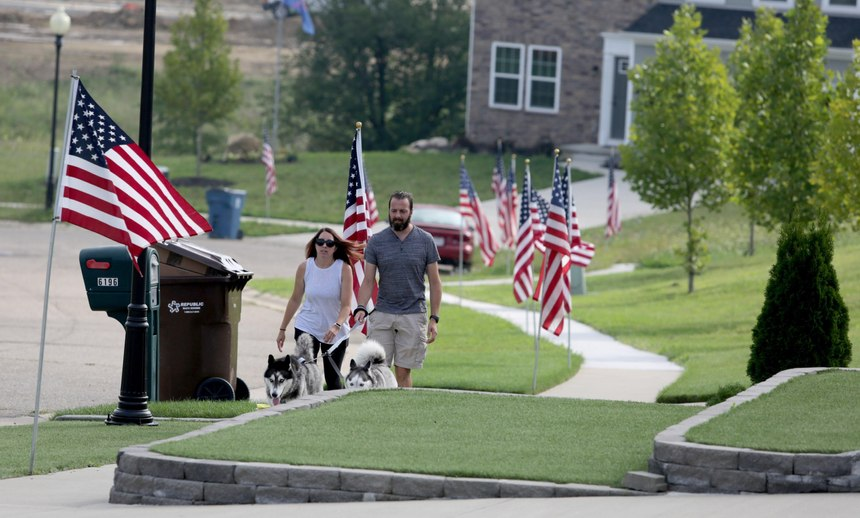 A couple walks their dogs Thursday morning along a line ofU.S.flags in the Bishop Meadows neighborhood. Roughly 300 flags have been placed in front yards throughout the subdivision to remember 9/11,U.S.military veterans, police officers and firefighters.