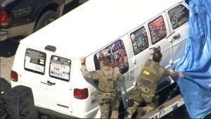 This frame grab from video provided by WPLG-TV shows FBI agents covering a van after the tarp fell off as it was transported from Plantation, Fla., on Friday, Oct. 26, 2018, that federal agents and police officers have been examining in connection with package bombs that were sent to high-profile critics of President Donald Trump. The van has several stickers on the windows, including American flags, decals with logos and text. (WPLG-TV via AP)