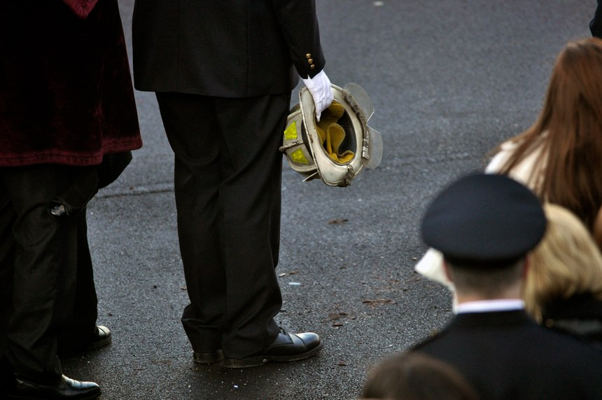 Nicholas Chiapperini holds the helmet of his father, Lt. Mike Chiapperini, during a funeral service in Webster, N.Y. Lt. Mike Chiapperini and fellow firefighter Tomasz Kaczowka were slain by a gunman in a fiery Christmas Eve ambush. (AP Photo/Kevin Rivoli)