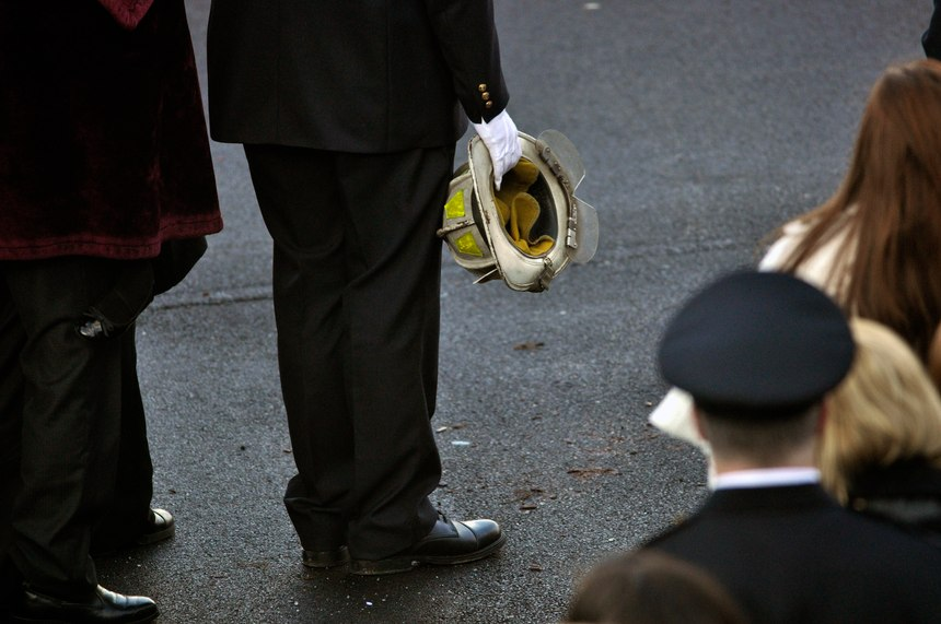 Nicholas Chiapperini holds the helmet of his father, Lt. Mike Chiapperini, during a funeral service in Webster, N.Y. Lt. Mike Chiapperini and fellow firefighter Tomasz Kaczowka were slain by a gunman in a fiery Christmas Eve ambush.