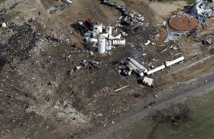 This April 18, 2013, aerial photo shows a crater, bottom left, the the remains of a fertilizer plant destroyed by an explosion in West, Texas. The massive explosion at the West Fertilizer Co. killed at least 14 people and injured more than 160. (AP Photo/Tony Gutierrez)