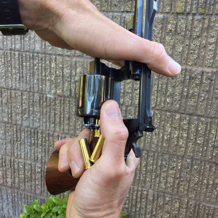 With the cylinder open, point the muzzle toward the sky and push downward on the tip of the ejector rod to unload the cylinder. Unfired cartridges may fall out by gravity – without pushing the ejector rod – when you point the muzzle skyward, and you can catch them in your hand to prevent them from falling onto the ground. Fired cases will often require you to push on the ejector rod though, as shown. (Photo/Mike Wood)