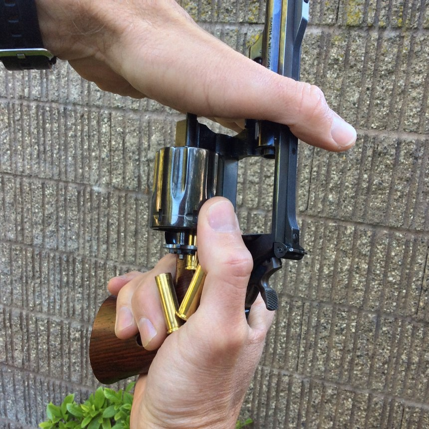 With the cylinder open, point the muzzle towardthe sky and push downwardon the tip of the ejector rod to unload the cylinder. Unfired cartridges may fall out by gravity – without pushing the ejector rod – when you point the muzzle skyward, and you can catch them in your hand to prevent them from falling onto the ground. Fired cases will often require you to push on the ejector rod though, as shown.