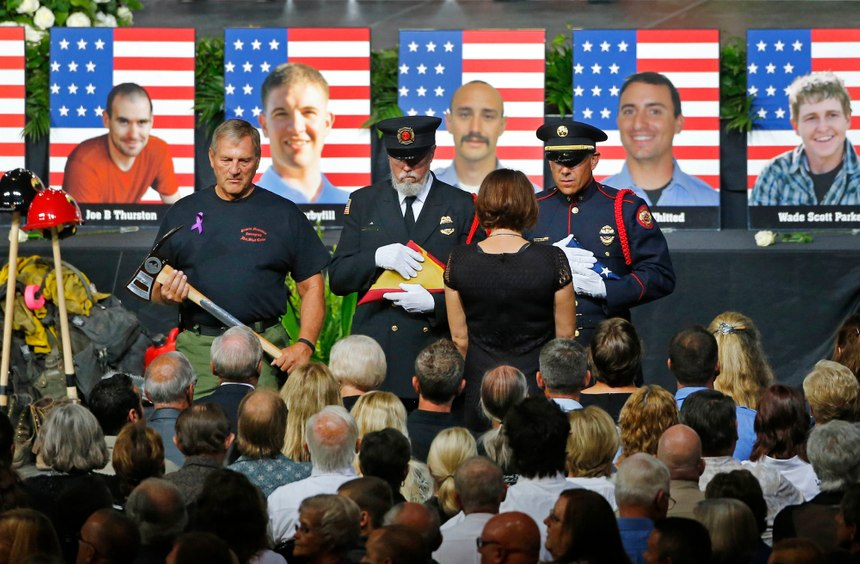 An honor guard presents families with an American flag during a memorial service in Prescott Valley, Arizona, Tuesday, July 9, 2013, for the 19 Granite Mountain hotshot firefighters that were killed while battling the Yarnell Hill Fire. (AP Photo/The Arizona Republic, David Kadlubowski, Pool)