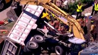 Firefighters extricate driver pinned in crushed truck