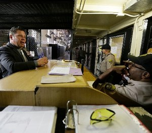Warden Ronald Davis, left, talks with guards on duty in the east block of death row at San Quentin State Prison Tuesday, Aug. 16, 2016, in San Quentin, Calif. (AP Photo/Eric Risberg)