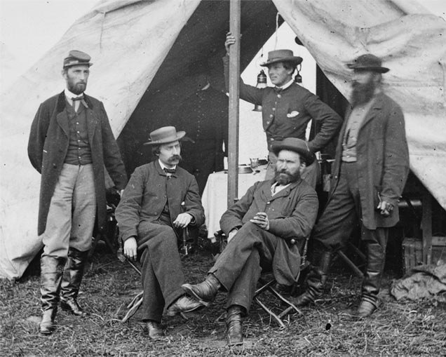 In this photo, Allan Pinkerton is sitting on the right. It is believed the person standing directly behind him is Kate Warne.