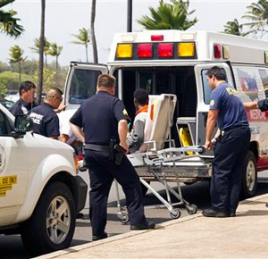 A 16-year-old boy who stowed away in the wheel well of a flight from San Jose, Calif., to Maui, on stretcher at center, is loaded into an ambulance at Kahului Airport in Kahului, Maui, Hawaii Sunday afternoon, April 20, 2014.  (AP Photo/The News, Chris Sugidono)